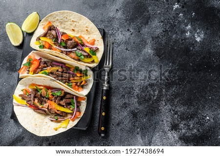 Mexican tacos shells with beef meat, onion, tomato and sweet pepper. Black background. Top view. Copy space.