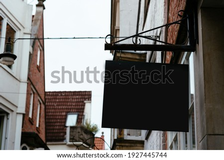 Blank store signage sign design mockup against medieval town. Clear shop template. Street hanging mounted hanging on the wall. Signboard for logo presentation