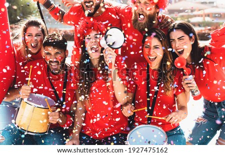 Football fans watching soccer match event at stadium - Young people having fun supporting favorite club - Sport entertainment concept  Royalty-Free Stock Photo #1927475162