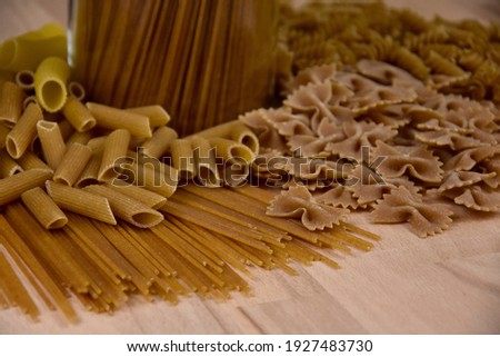 Different types of dried pasta stock images. Group of dried uncooked wholemeal pasta on the table stock images. Mixed uncooked italian pasta close-up photo