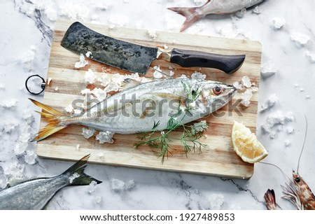 From above of raw scad with lemon slice and cleaver on wooden cutting board with fresh dill sprig Royalty-Free Stock Photo #1927489853