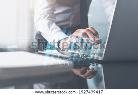 Business finance technology, digital marketing, E-business concept. Businessman working with laptop computer analyzing sales data in office with economic growth, financial graph. Business strategy