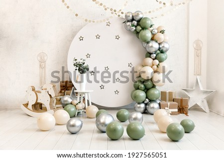 Birthday decorations - gifts, toys, balloons, garland and number for little baby party event on a white wall background. Royalty-Free Stock Photo #1927565051