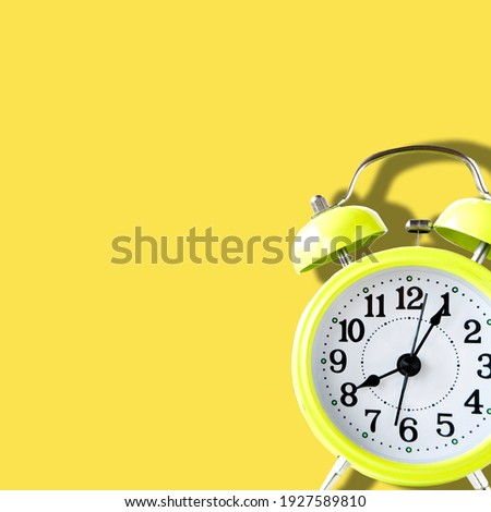 Yellow alarm clock at eight in the morning on yellow background with space for text in square size image