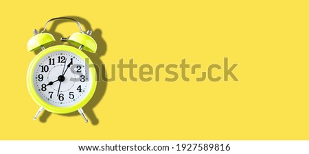 Yellow alarm clock on yellow background with space for text in banner size image