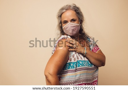 Portrait of a senior woman with protective face mask showing her arm with bandage after getting vaccine. Mature woman sitting against brown background after receiving corona virus vaccination. Royalty-Free Stock Photo #1927590551