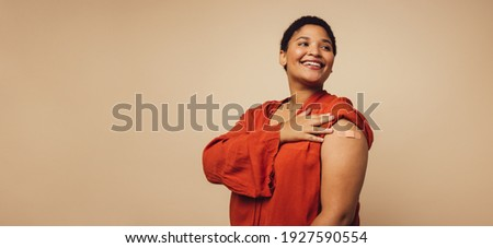 Woman showing her arm after receiving vaccine shot on brown background. Female with bandage on her arm looking away and smiling. Royalty-Free Stock Photo #1927590554