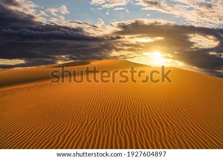 Sunset over the sand dunes in the desert. Arid landscape of the Sahara desert Royalty-Free Stock Photo #1927604897