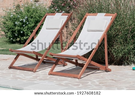 Swim pool with clear blue water and two sun bed on sunny day in a yard, beautiful vacation for relaxation and leisure, concept of mindfulness well being, happiness and slow life Royalty-Free Stock Photo #1927608182