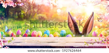 Abstract Defocused Easter Scene - Ears Bunny Behind Grass And Decorated Eggs In Flowery Field Royalty-Free Stock Photo #1927626464