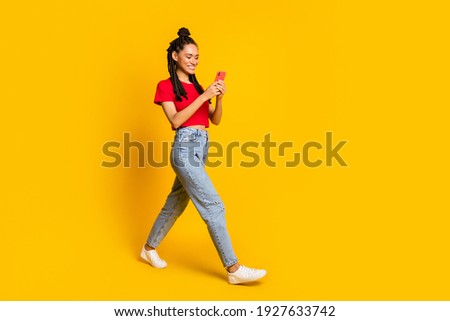 Full length body size view of lovely focused cheerful girl going using device app 5g isolated bright yellow color background