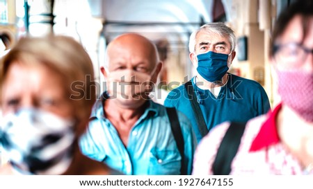 Urban crowd of adult citizens walking on city street during pandemic - New reality life style concept with senior people with covered faces - Selective focus on man with blue protective mask Royalty-Free Stock Photo #1927647155