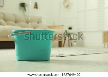 Water dripping from ceiling into plastic bucket on floor in living room, space for text. Leaking roof Royalty-Free Stock Photo #1927649402
