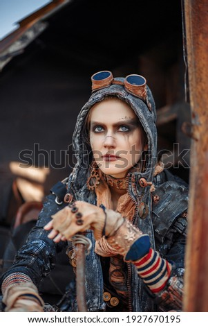 A girl in an apocalyptic world. A girl sits on a pile of iron in an apocalyptic world. Post-apocalypse. Apocalyptic. Royalty-Free Stock Photo #1927670195