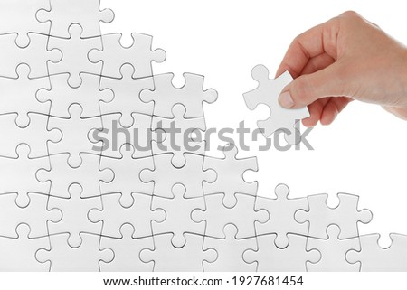 Human female hand trying to connect white puzzle piece isolated on white background. Doing or making a jigsaw puzzle trying connection find solution strategy concept image. reconstruction, rebuilding Royalty-Free Stock Photo #1927681454