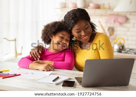 Happy African American Mom And Her Cute Little Daughter Using Laptop Together In Kitchen, Black Family Having Fun At Home, Embracing And Watching Cartoons Or Kids Development Videos Online, Free Space