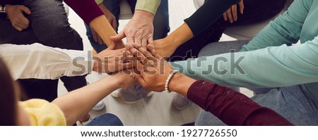 People of different ages and nationalities fold their hands on each other, symbolizing their unity and support. Team of people who are set up for productive work and a positive result. Close up. Royalty-Free Stock Photo #1927726550