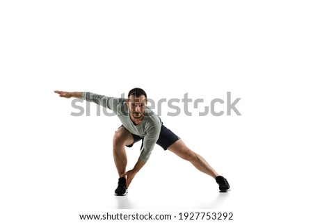 Stretching. Young caucasian male model in action, motion isolated on white background with copyspace. Concept of sport, movement, energy and dynamic, healthy lifestyle. Training, practicing. Authentic Royalty-Free Stock Photo #1927753292