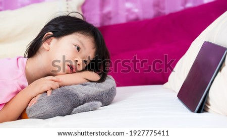New normal lifestyle concept. Cropped shot Asian kid lying on soft bed watching cartoons on tablet. A 3-4 years old child listen music on touch pad. Girl have fun and relaxing on her own in bedroom.