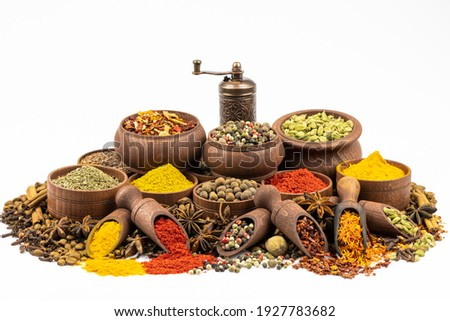 Assortment of east spices and seasonings in wooden tableware by close up isolated on a white background. Royalty-Free Stock Photo #1927783682