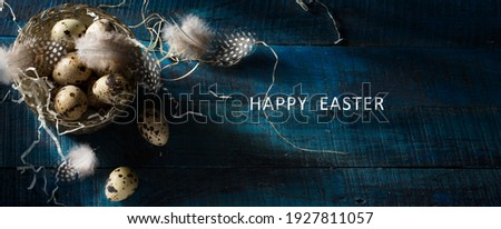 Happy Easter banner background; Retro style picture with Easter eggs and feathers in silver basket  on dark blue background with copy space.