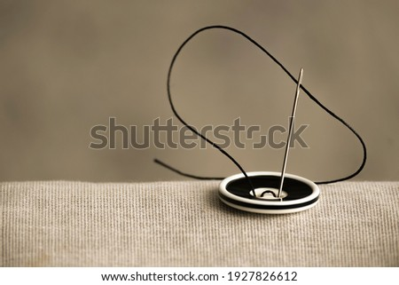 The black and white button is sewn with a sewing needle and black thread to hold the two fabrics together in close-up. A vintage-style photo for an article about the sewing hobby and sewing. Royalty-Free Stock Photo #1927826612