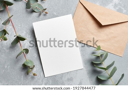 Wedding invitation card mockup with envelope and eucalyptus branches on grey concrete background, top view Royalty-Free Stock Photo #1927844477