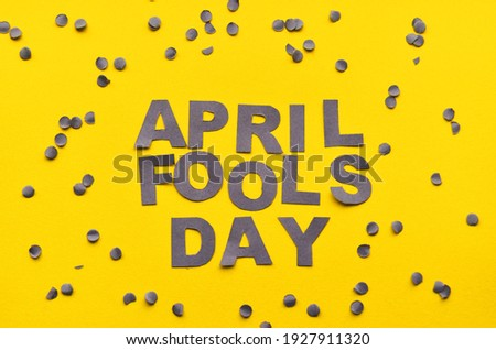 Image caption April Fools' Day of carved letters of grey on a yellow background around scattered confetti. High quality photo