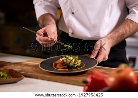 chef dressing salad with fresh greens, adding finishing touch on dish before it is going to be served for restaurant guests Royalty-Free Stock Photo #1927956425