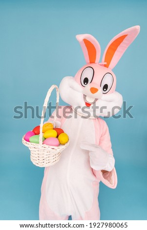 Easter bunny or rabbit or hare with basket of colored eggs, shows index finger, having fun, celebrates Happy easter. Easter rabbit isolated on blue background