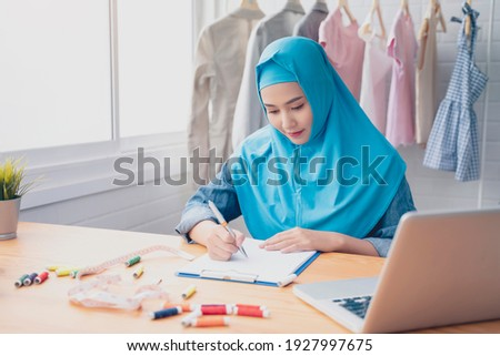 Asian Muslim woman fashion designer job occupation working in clothing textile workshop modern office signing contract with computer laptop, business deal partnership with distributers manufacturers