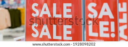 Red bright sale banner on anti-thieft gate sensor at retail shopping mall entrance.Seasonal discount offer.Discount information at store entrance, shopping season promotion.Large red panels.web banner