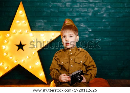 Child taking photos in professional photo studio. Beautiful smiling boy holding a camera. Young photographer. Happy child photographer with film camera. Cute kid takes picture with vintage camera