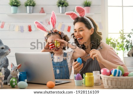 Mother and her daughter painting eggs. Happy family preparing for Easter. Cute little child girl wearing bunny ears. Royalty-Free Stock Photo #1928116109