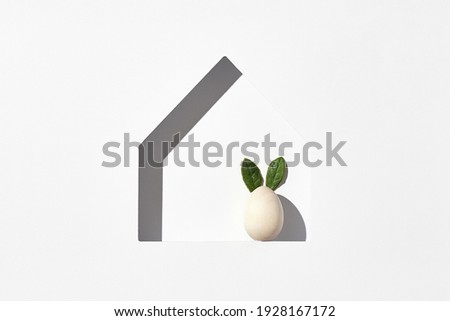 Easter minimal background with house silhouette and eggs. Sunshine with harsh shadow. Happy easter 2021 creative concept. Flat lay, top view Royalty-Free Stock Photo #1928167172
