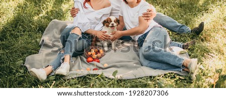 Beautiful young family in white t-shirt and jeans relaxing with little white and brown dog in the park in summer. Sit on a gray blanket, hug. Camping, forest, sunny day. After quarantine coronavirus.