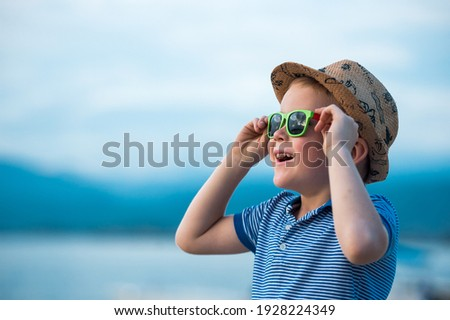 Portrait of happy child in sunglasses on the beach. Summer vacation concept. Smiling kid boy in hat and glasses near sea. Royalty-Free Stock Photo #1928224349