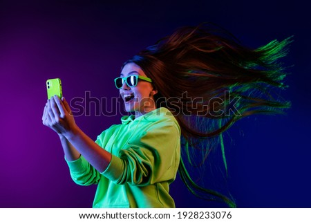 Photo of amazed shocked young woman look phone fast internet fly hair isolated on colorful neon background Royalty-Free Stock Photo #1928233076