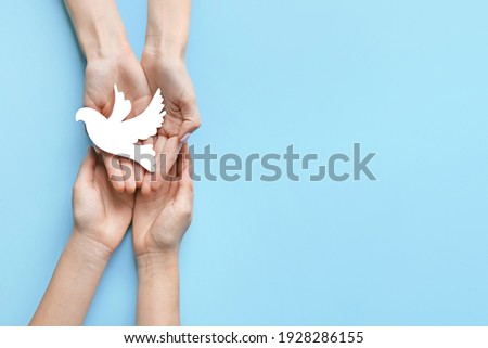 Female hands with paper dove on color background. International Day of Peace Royalty-Free Stock Photo #1928286155
