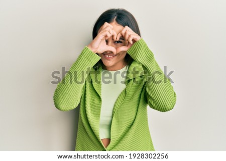 Young brunette woman wearing casual clothes doing heart shape with hand and fingers smiling looking through sign  Royalty-Free Stock Photo #1928302256