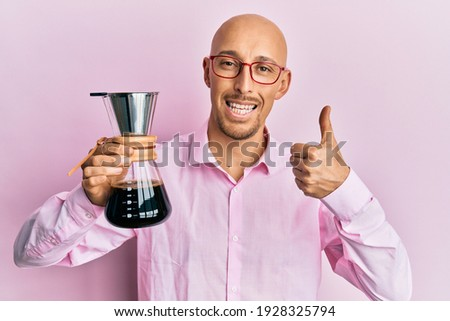 Bald man with beard holding coffee maker with filter smiling happy and positive, thumb up doing excellent and approval sign