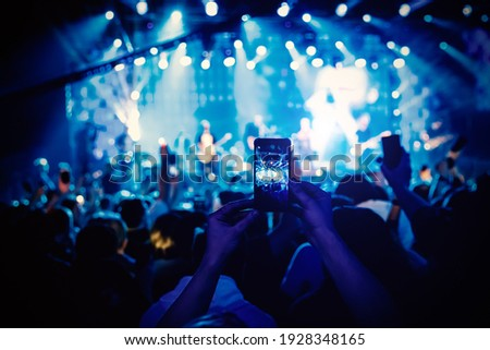 Man takes a picture of the show at the concert hall using a smartphone Royalty-Free Stock Photo #1928348165