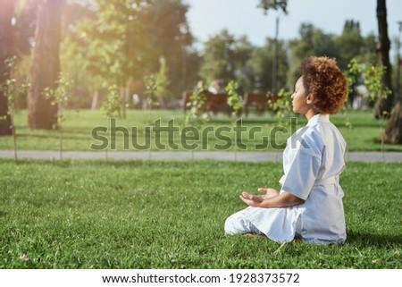 Cute little girl karateka doing meditation exercise outdoors Royalty-Free Stock Photo #1928373572