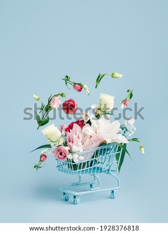 Shopping trolley with flying flowers on pastel blue background. Flower delivery concept with copy space. Sale, shopping for the holidays, Mothers Day, Women's Day, Valentines Day or Birthday.