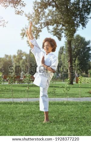 Cute female child karateka doing exercise outdoors Royalty-Free Stock Photo #1928377220