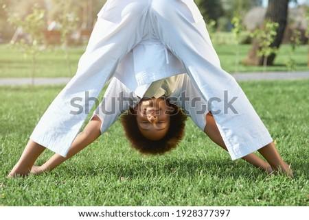 Adorable female child karateka doing exercise outdoors Royalty-Free Stock Photo #1928377397