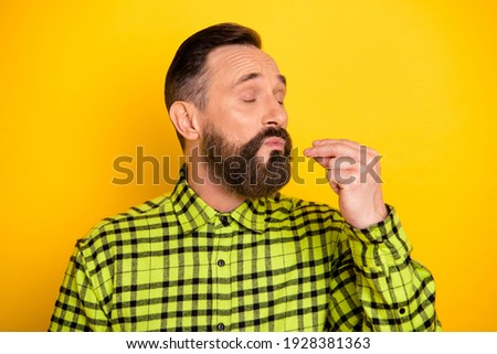 Photo of mature man show fingers tasty yummy delicious perfect sign chef isolated over yellow color background Royalty-Free Stock Photo #1928381363