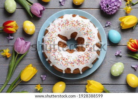 Glazed Easter cake with sprinkles, painted eggs and flowers on grey wooden table, flat lay