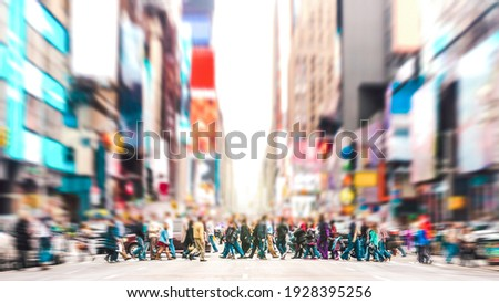 Defocused background of people walking on zebra crossing on 7th avenue in Manhattan - Crowded streets of New York City during rush hour in urban area - Vivid sunset filter with soft sharp focus Royalty-Free Stock Photo #1928395256