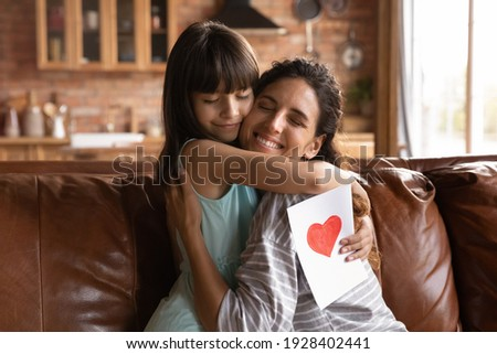 Cute small Latino 8s girl child hug happy young mother congratulate with birthday give handmade postcard. Loving little daughter embrace Hispanic mom greeting with woman day present gift card. Royalty-Free Stock Photo #1928402441